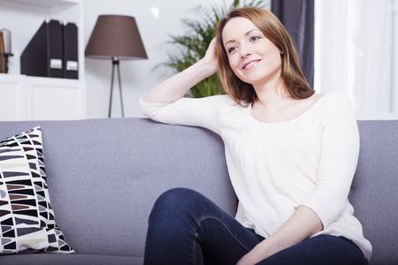 Mooi bruin haired lachende meisje casual gekleed, zittend op een sofa