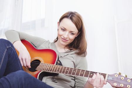 Mooi casual gekleed meisje met lang bruin haar spelen een lied op gitaar terwijl ze op de vloer zitten