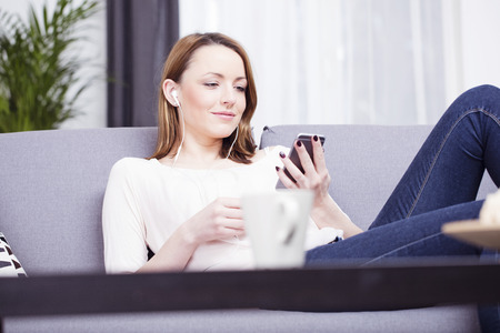 brown haired girl: Happy smiling brown haired girl relaxing on sofa while using her smarthpone with earphones