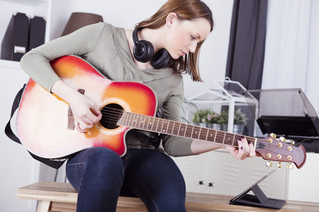 Mooi bruin haired meisje met een koptelefoon op haar nek te spelen een aantal records op haar gitaar terwijl het kijken op tablet Stockfoto