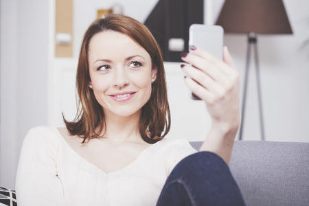 brown haired girl: Attractive brown haired girl sitting on a sofa having a video call or taking a selfie