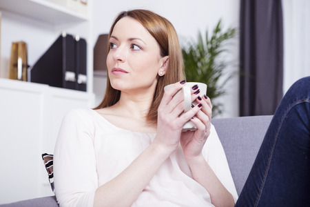 Mooi bruin haired meisje met een rust op de bank genieten van haar mok met koffie of thee