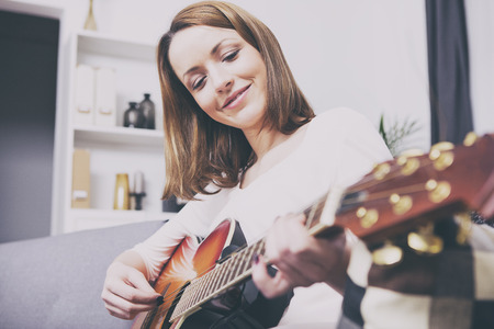 brown haired girl: Attractive brown haired girl sitting smiling on couch playing some music with her guitar