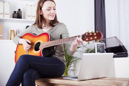 Muy sonriente haires castaño chica vestida sentada en una mesa de jugar los registros en la guitarra apoyada por la computadora portátil Foto de archivo