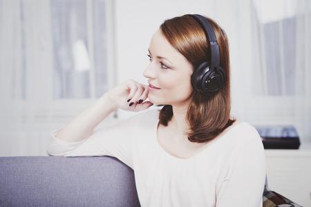 Het aantrekkelijke jonge meisje geniet van luisterend aan muziek met hoofdtelefoons op laag Stockfoto