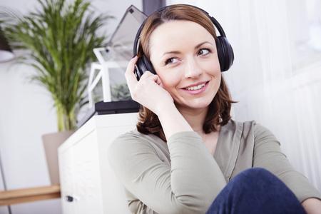 Gelukkig jong bruin haired meisje zittend op de bank met een hoofdtelefoon genieten van het luisteren naar muziek