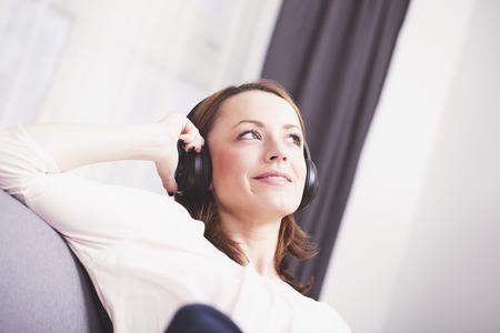 Aantrekkelijk gelukkig bruin haired meisje met een koptelefoon lachend op comfortabele bank zitten Stockfoto