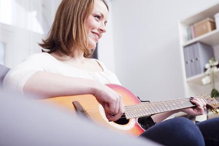 Mooi bruin haired meisje smiling op de bank genieten van het spelen van een aantal records met gitaar Stockfoto