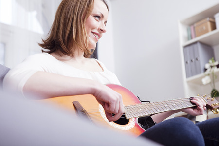 Beautiful brown haired girl sitting smiling on sofa enjoying playing some records with guitar