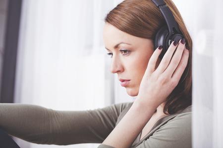 Peinzend bruine haren meisje zitten luisteren naar muziek met een hand op hoofdtelefoon