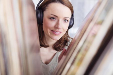 Gelukkig glimlachend bruine haren meisje met koptelefoon op zoek naar records in een plank