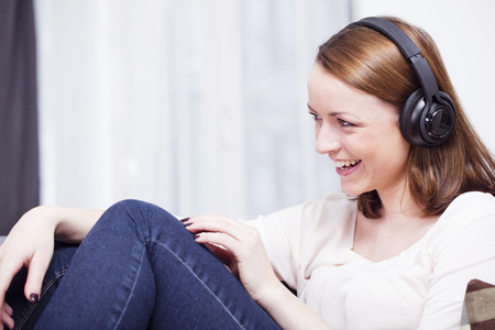 Laughing brown haired young girl listening to music with headphones relaxing on couch