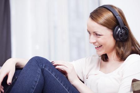Lachend bruin haired jonge meisje luisteren naar muziek met een koptelefoon ontspannen op de bank