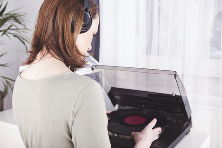 Happy young woman with headphones putting record into the player, from behind Standard-Bild