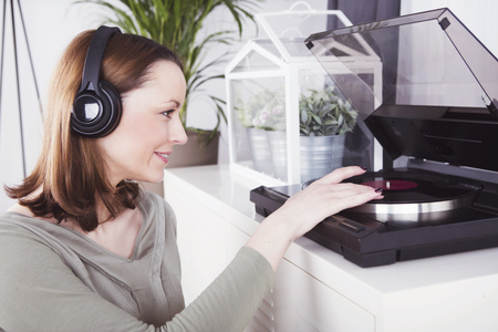 brown haired girl: Smiling brown haired girl sitting in front of a record player enjoying listening to music Stock Photo