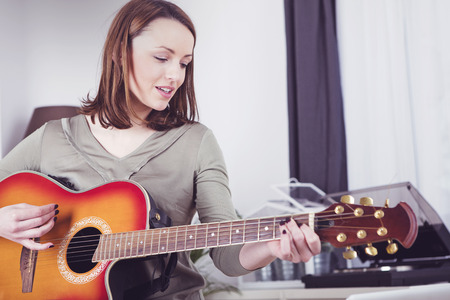 Happy brown haired smiling girl playing some records on guitar Standard-Bild