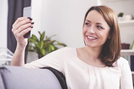 Mooi bruin haired meisje dat een selfie  praten met iemand via een video-oproep op een sofa zitten