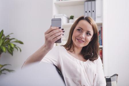 Mooie jonge bruine haired meisje dat een selfie of het hebben van een videochat zittend op de bank