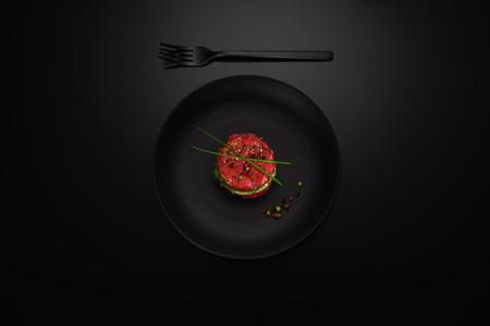 Beef tatar as a snack on a black mat plate, black matte background, shot from above.