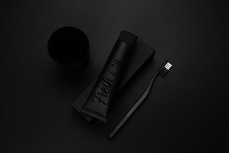 A set of black toothpaste, toothbrush and cup for brushing your teeth against a black background