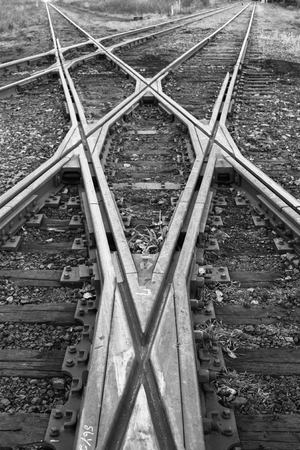 merging train tracks in black and white