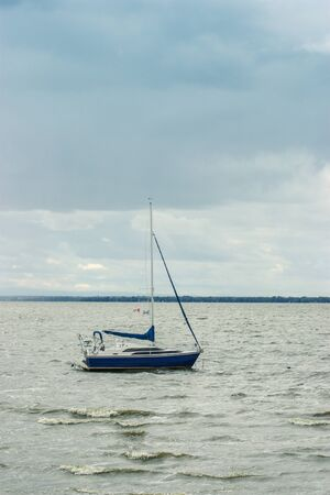 sailing boat alone on a cloudy day Stock Photo