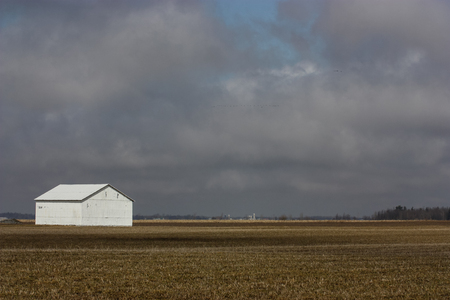white barn in a field on a cloudy day Stock Photo