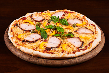 alcaparras: Chicken pastrami, yellow pepper and capers pizza on a wooden table