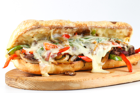 Tasty beef steak sandwich with onions, mushroom and melted provolone cheese in a ciabatta Stock Photo