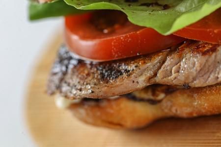 steak sandwich: Tasty pork steak sandwich in a ciabatta with tomatos, lettuce, mayonnaise and barbecue sauce Stock Photo