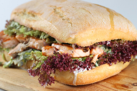 steak sandwich: Tasty salmon steak sandwich in a ciabatta with lettuce, scallion sauce, capers, dill and basil