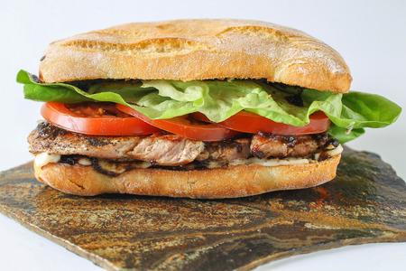 Tasty sandwich au porc steak dans une ciabatta avec des tomates, de la laitue, la mayonnaise et la sauce barbecue Banque d'images - 52275514