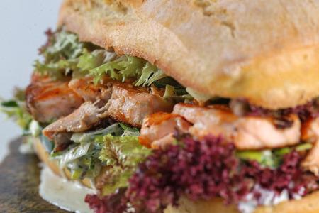 scallion: Tasty salmon steak sandwich in a ciabatta with lettuce, scallion sauce, capers, dill and basil