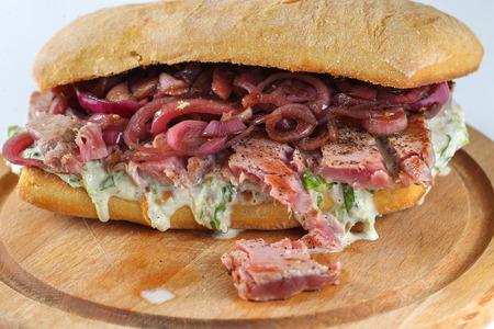 steak sandwich: Tasty tuna steak sandwich in a ciabatta with lettuce, onions, Marie Rose sauce and lemon juice
