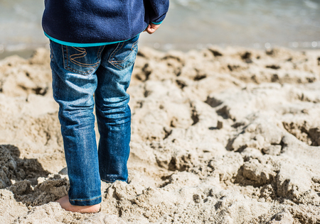 Little boy stands on the sand near the sea