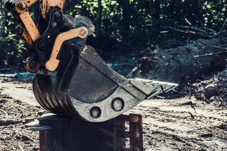 sand quarry: Excavator bucket parked on another excavator excavator.