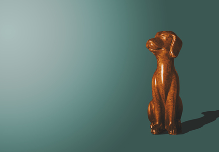 Wooden, gold doggy figurine. The wooden dog looks up with a satisfied face. A view of a dog who sits on a dark pastel background. Animal concept, minimalism concept. Stock Photo