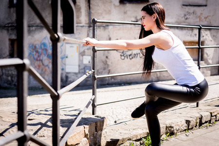 Attractive spontaneous woman exercising outdoors. Authenticity and Spontaneity. The girl is performing an authentic warm-up. The girl does physical exercises, care for her figure. Playing sports. Foto de archivo