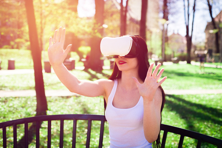 Virtual reality, fun in the park. A woman relaxes in the park using VR. The girl imagines that she is climbing the rope. Spending free time outside, lifestyle concept.