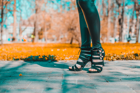 Legs view of a woman walking.The girl in black pants moves around park outside. Beuty and fashion concept. Stock Photo