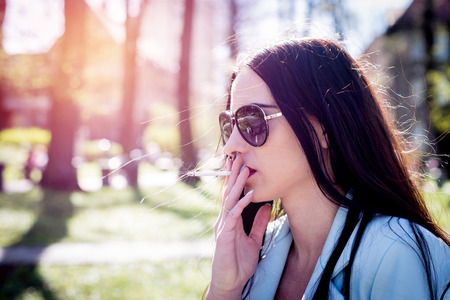 Closeup of a woman's face smoking a cigarette. An attractive girl in sunglasses holds a cigarette in her mouth. Stressed female satisfies nicotine craving. Health concept, retro.