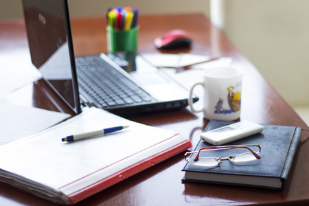 documenting: calendar, laptop and coffee cup on office wooden table Stock Photo