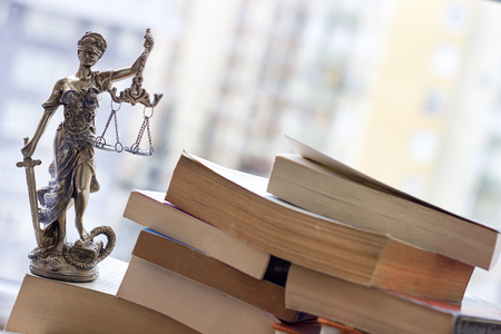 review: Justice statue with sword and scale and books. Law concept Stock Photo