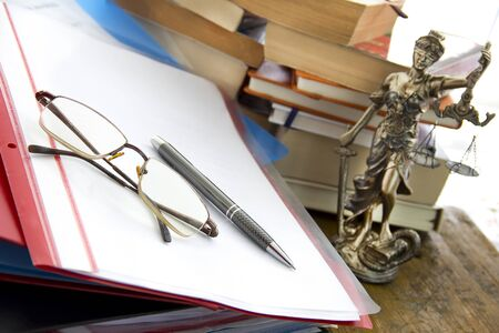 justice statue: Justice statue with sword and scale, folders and books. Law concept Stock Photo