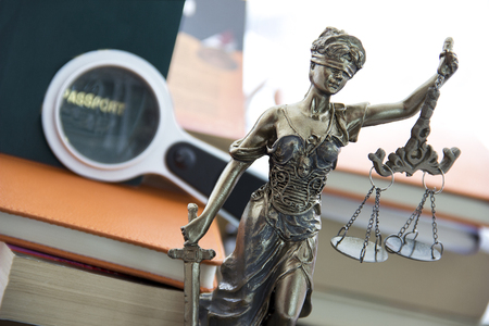 justice statue: Travel law. Justice statue with sword and scale and special passport Stock Photo