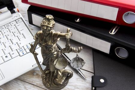 justness: Law concept, statue, laptop and folder on wood table Stock Photo