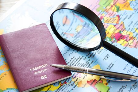 duty belt: Travel planning over world map. Passport and magnifying glass Stock Photo