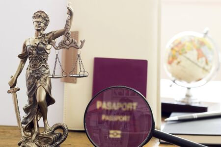 justness: Law concept, statue, magnifying glass, Passport and world map. Travel