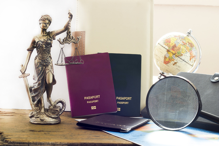 Law concept, statue, magnifying glass, Passport and world map. Travel