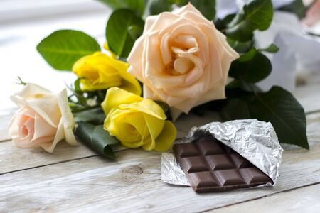 Yellow and peach-colored roses, coffee and slices of chocolate on the wooden table